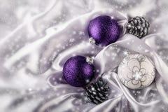 Les cônes de luxe de pin argenté de boules de Noël sur la décoration blanche de Noël de satin ont combiné des couleurs pourpres e Image stock
