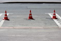 Les cônes en plastique du trafic de signalisation enferme un endroit dans le parking pour des voitures Images libres de droits