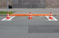 Les cônes en plastique du trafic de signalisation enferme un endroit dans le parking pour des voitures Image stock