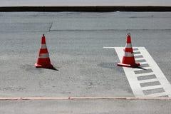 Les cônes en plastique du trafic de signalisation enferme un endroit dans le parking pour des voitures Images stock