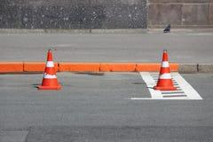 Les cônes en plastique du trafic de signalisation enferme un endroit dans le parking pour des voitures Photo libre de droits