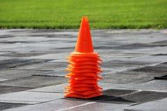 Les cônes oranges en plastique de signal se tiennent au stade en vue de la concurrence pour les poids de levage Images stock