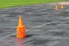 Les cônes oranges en plastique de signal se tiennent au stade en vue de la concurrence pour les poids de levage Photographie stock libre de droits