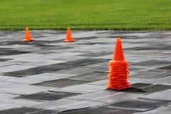 Les cônes oranges en plastique de signal se tiennent au stade en vue de la concurrence pour les poids de levage Photo stock