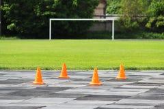 Les cônes oranges en plastique de signal se tiennent au stade en vue de la concurrence pour les poids de levage Photos stock