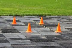 Les cônes oranges en plastique de signal se tiennent au stade en vue de la concurrence pour les poids de levage Image libre de droits