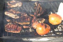Les côtelettes et les tomates d'agneau sur un charbon de bois grillent Photographie stock