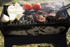 Les côtelettes, les tomates et les oignons d'agneau sur un charbon de bois grillent Photo libre de droits
