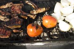 Les côtelettes, les tomates et les oignons d'agneau sur un charbon de bois grillent Photographie stock