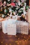 Les cadeaux dans des sacs en papier sont sur le plancher en bois à l'arbre de Noël images stock