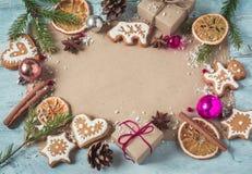 Les cadeaux de fond, les biscuits de Noël et le sapin s'embranche un bleu de retour Image stock
