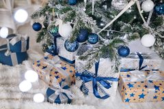 Les cadeaux de Noël enveloppés en papier argenté et bleu, fond avec Noël allume le bokeh de brouiller sous l'arbre de Noël photo libre de droits