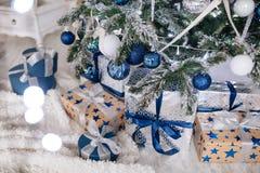 Les cadeaux de Noël enveloppés en papier argenté et bleu, fond avec Noël allume le bokeh de brouiller sous l'arbre de Noël image libre de droits