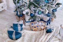 Les cadeaux de Noël enveloppés en papier argenté et bleu, fond avec Noël allume le bokeh de brouiller sous l'arbre de Noël photographie stock libre de droits