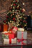 Les cadeaux de Noël enveloppés en papier brun et rouge dans le grenier, fond avec Noël allume le bokeh de l'arbre de Noël brouill photos stock