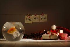 Les cadeaux de Noël, les guirlandes rougeoyantes et les signes de nouvelle année derrière les poissons d'or brouillés dans l'aqua images libres de droits