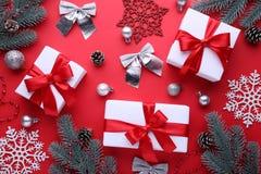 Les cadeaux de Noël présente avec des décorations sur un fond rouge photos libres de droits