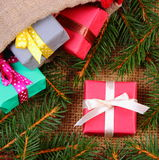 Les cadeaux enveloppés dans le jute mettent en sac pour Noël ou d'autres branches de célébration et impeccables Image libre de droits