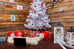 Les cadeaux se trouvent sous un arbre de Noël décoré dans un coin Photographie stock libre de droits