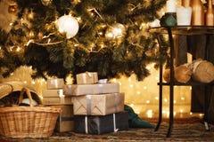 Les cadeaux sous l'arbre de Noël allume le fond 2018 photos stock