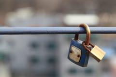 Les cadenas de couples sont verrouillés sur le rail avec le fond brouillé de ville, symbole éternel d'amitié ou aiment pour toujo Photographie stock