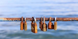 Les cadenas rouillés se sont fermés sur l'amour de clôture épluché de signalisation Fermez-vous vers le haut de la vue, fond brou Photo stock