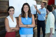Les cadres commerciaux féminins de sourire se tenant avec des bras ont croisé dans le bureau Photos libres de droits