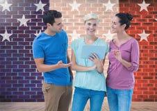 Les cadres discutant au-dessus du comprimé numérique contre le mur de briques avec l'étoile forme Photo libre de droits