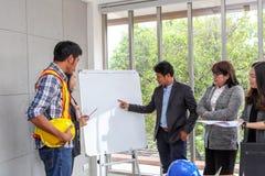 Les cadres expliquent des plans sur un tableau blanc Bossage confiant images libres de droits