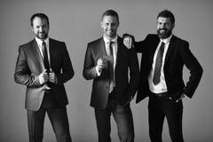 Les cadres font de la publicité la société et l'association sur le fond gris-clair Les hommes d'affaires portent les costumes et  image stock