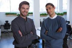 Les cadres masculins se tenant avec des bras ont croisé dans le bureau Image libre de droits