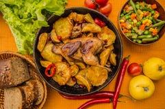 Les cailles ont fait cuire au four dans une casserole avec des pommes de terre et des pommes Sur le fond d'or Vue supérieure Plan Photographie stock libre de droits