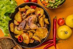 Les cailles ont fait cuire au four dans une casserole avec des pommes de terre et des pommes Sur le fond d'or Vue supérieure Plan Photos libres de droits