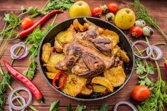 Les cailles ont fait cuire au four dans une casserole avec des pommes de terre et des pommes Sur le fond en bois brun Vue supérie Photo libre de droits