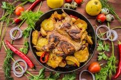 Les cailles ont fait cuire au four dans une casserole avec des pommes de terre et des pommes Sur le fond en bois brun Vue supérie Images stock