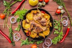 Les cailles ont fait cuire au four dans une casserole avec des pommes de terre et des pommes Sur le fond en bois brun Vue supérie Photos libres de droits