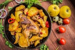 Les cailles ont fait cuire au four dans une casserole avec des pommes de terre et des pommes Sur le fond en bois brun Vue supérie Photos stock