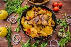Les cailles ont fait cuire au four dans une casserole avec des pommes de terre et des pommes Sur le fond en bois brun Vue supérie Image libre de droits