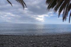 Les cailloux échouent avec des vagues et exposent au soleil la réflexion, ciel bleu, temps nuageux Images stock