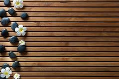 Les cailloux de massage et les fleurs noirs de station thermale ont placé sur le conseil en bois Image libre de droits