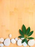 Les cailloux encadrent avec la feuille sur le bambou   fond Photographie stock libre de droits