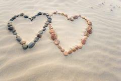 Les cailloux ont arrangé dans la forme de deux coeurs sur des ondulations de plage de sable Photos stock
