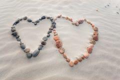 Les cailloux ont arrangé dans la forme de deux coeurs sur des ondulations de plage de sable Photographie stock libre de droits