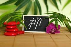 Les cailloux rouges ont arrangé dans le mode de vie de zen avec une orchidée, une bougie allumée, une branche en bambou et le feu Photographie stock libre de droits