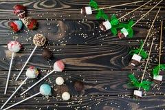 Les cakepops et les guimauves colorés de chocolat ont placé sur le fond en bois photo stock