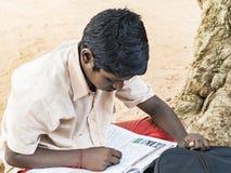 Les camarades de classe de garçon ont concentré l'étude avec le livre se reposant sur le plancher extérieur au terrain de jeu d'é photo libre de droits