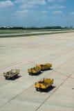 Les camions jaunes attendent le chargement dans la plate-forme de l'aéroport Images stock