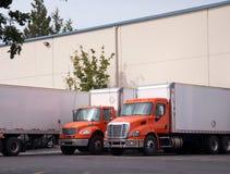 Les camions oranges de milieu semi avec des remorques de boîte se tiennent dans l'entrepôt d Photos stock