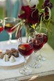 Les candys et les verres de truffes de chocolat avec le vin rouge sur le blanc courtisent Photo stock