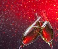 Les cannelures de Champagne avec de l'or bouillonne sur le fond clair rouge et violet de bokeh Photos stock